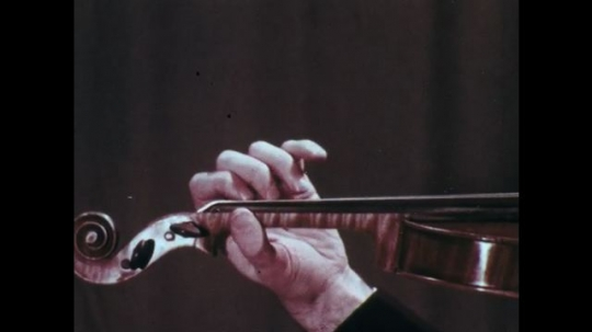 1970s: Hand shakes while playing violin. Different view of hand.