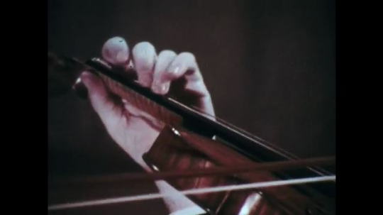 1970s: Hand moves rapidly across violin strings. Man plays violin, his fingers rapidly pressing the strings.