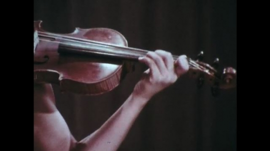 1970s: Bare arm plays violin, shifting between different parts of the bridge. Young woman plays violin.