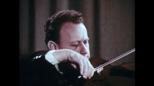 1970s: Man with suit plays violin in room with curtained background.