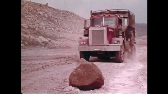 1970s: UNITED STATES: truck drives carefully on dust track. View through windshield of truck. Side profile of man in cabin of truck
