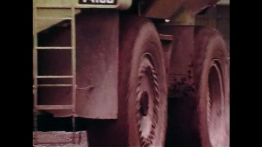 1970s: UNITED STATES: vehicles drive along quarry tracks. Grabber on truck