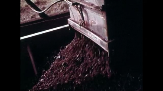 1970s: UNITED STATES: machine unloads coal into train carts. Train on tracks. Red light flashes
