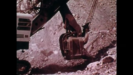 1970s: UNITED STATES: bucket gathers coal. Man inspects underneath truck. Man operates vehicle. Man injured under vehicle