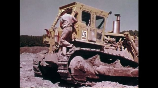 1970s: UNITED STATES: man climbs down tread on vehicle. Man climbs up ladder onto truck. Vehicle in mud. Close up of boots on step. Electric cable