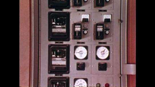 1970s: UNITED STATES: electric switch board and controls. Vehicle operates with lights at night. Machine moves coal at night. View across mine area
