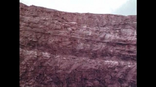 1970s: UNITED STATES: view of rock face. Track through quarry area. Sediments in rock face.  Man on top of vehicle in quarry