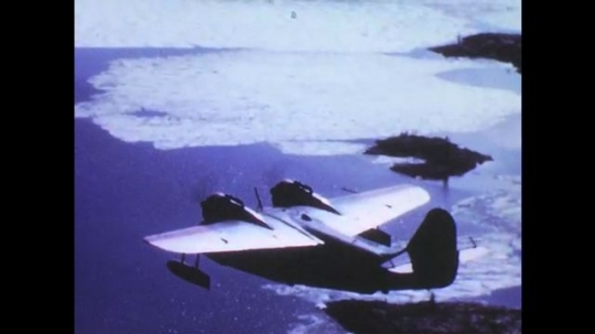 1960s: UNITED STATES: Plane flies in sky over ocean. Man drills into rock. Man operates drag line