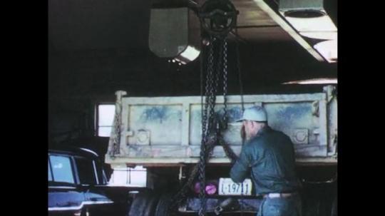 1960s: UNITED STATES: man pulls down on lifting chain. Man puts blocks under vehicle. Man works under vehicle.