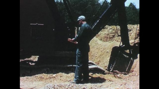 1960s: UNITED STATES: man reports on accident site by digger. Man with clipboard. Men looks at injured leg