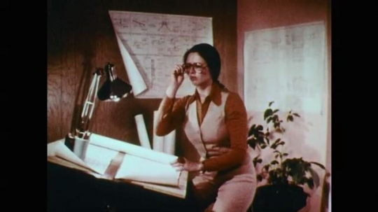 1970s: Business woman sits at drafting table. Woman removes glasses. Woman stands, thrusts 3 fingers in air. Red ring pulsates. Superhero silver suited woman is outside with shield and moves scepter.