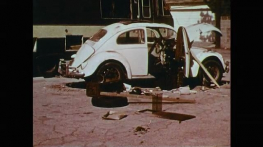 1970s: Abandoned white Volkswagen Beetle car sits in lot. Broken glass. Car door closes on wooden stick. Passenger train speeds by on track.
