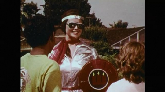 1970s: Superhero woman smiles and talks. Superhero woman salutes with shield. Boy and girl salute by holding up three fingers. Girl talks. Superwoman hero thrusts shield into sky and disappears.