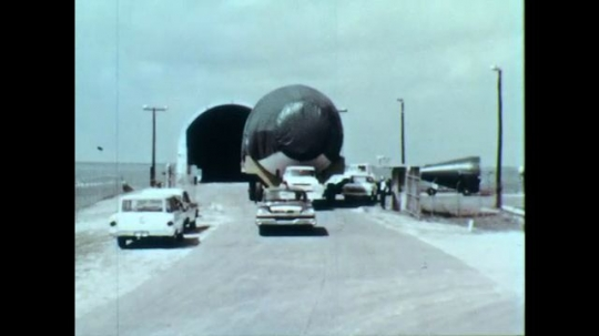 1960s: A piece of the Saturn C-1 rocket on the back of a semi-trailer truck. It is led down the road as part of a caravan of vehicles, toward Cape Canaveral Launch Complex 34.