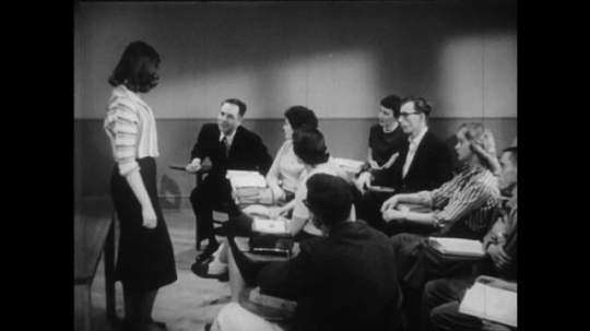 1950s: Young woman stands at the front of college classroom.  Woman sits.  Male professor gestures and stands.  Man speaks.