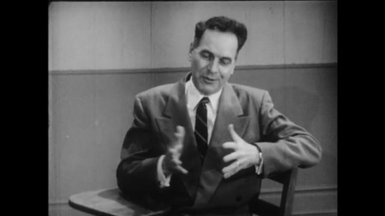 1950s: Male professor sits in classroom.  Man talks and gestures.  Young man speaks in front of chalkboard.