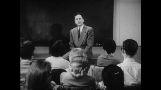 1950s: Male professor sits on desk and speaks to class.  Man reaches into pocket.  Student raises hand.  Man points at student.