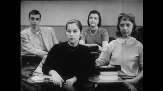 1950s: Male and female college students sit in classroom.  Male professor turns on tape player.  Man points.  Students listen.  Tape player reels spin.