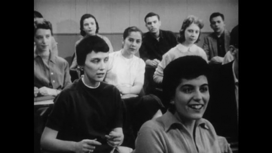 1950s: Young woman stands at front of college classroom.  Male and female students sit.  Students answer and laugh.  Woman responds.  Woman smiles.