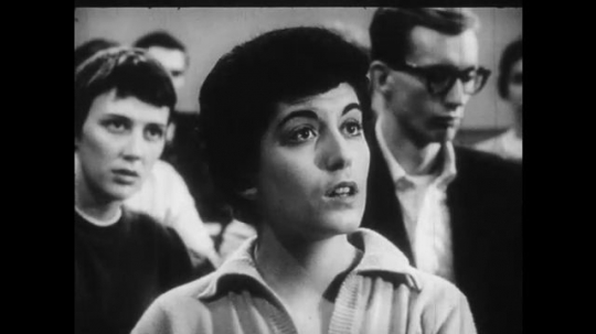 1950s: Young woman speaks from seat in college classroom.  Woman reads from book.  Male and female students listen.