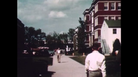 1940s: People walk on the sidewalk. People walk up the stairs to the building entrance. Car drives through.
