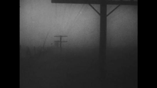 1930s: Foggy power line. The sun. Cars drive on foggy road. Flatlands with house. Man climbs out of underground shelter, closes door. Cows sit and stand next to house.