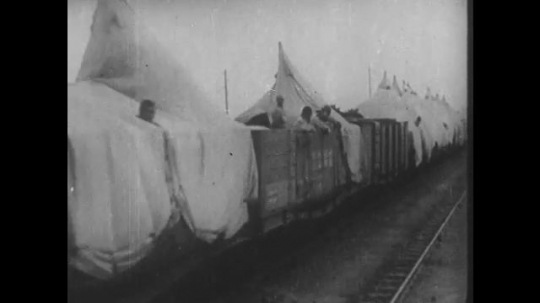 1930s: Train passes by, wagons full with soldiers. Soldiers leave wagons. Soldiers fire cannons. Soldiers run. Soldiers lay and shoot. General holds binoculars and points. Soldiers sit next to canon.