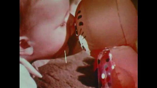 1970s: Curious baby lies on carpet, plays with toy bear balloon, bites and squeezes it.
