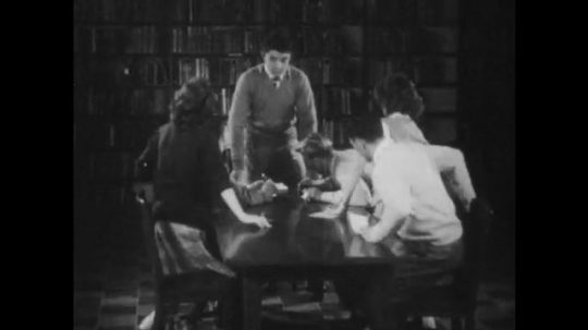 1940s: Students stand up, congratulate student at head of table. Two students stand in front of bulleting bulletin board, read paper. Student complains to the other student.