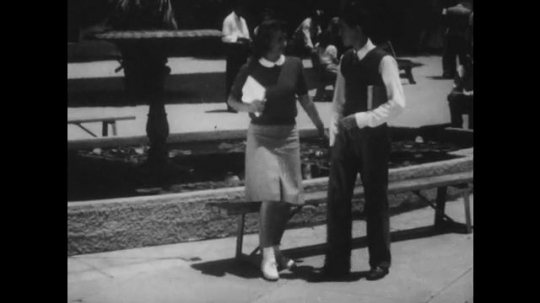 1940s: Female student stands up, walks next to male student. People stand at bar counter. The two students grab drinks. Male student plays jukebox. Female student smiles and moves slowly.