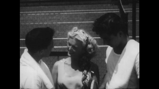 1940s: Two young men and a young woman chat on tennis court. Young woman walks away. Young man sits down on bench and ties his shoe. Young woman approaches and sits next to him, talks.