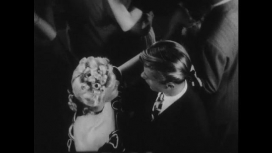 1940s: Students dance at school dance. Female student talks to male student while they dance.