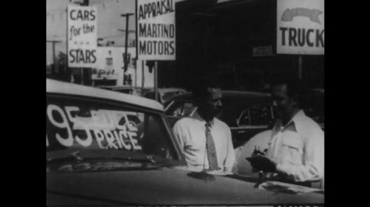 1940s: Car seller sells car to costumer. Two students talk and shake hands.