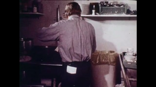 1970s: Man in dish washing area of restaurant kitchen screws lid onto container and sets on counter. He closes his satchel and carries the container out in his hand. He talks to server as he exits.