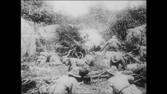 1910s: Confederate troops with hats hide behind rocks and fire rifles. Union soldiers on horseback fire guns in battle. wagon explodes in smoke on field. officer with gun dies in arms of man.