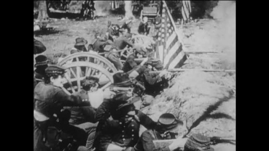 1910s: Union soldiers in uniform fire rifles and cannons, jump wall and charge Confederate troops on field during battle. men in uniform and woman wave hands and celebrate in living room.