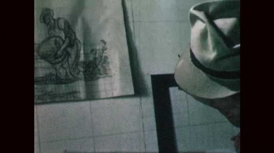 1940s: Man wearing fedora uses L square to draw grid within grid on canvas. Man consults with sketch of mural and draws on large canvas.