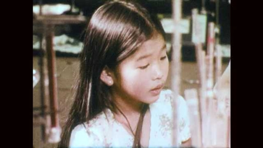 1970s: Close up of girl in lab. Close up of girl. View of scale. Hand puts metal piece on scale. Close up of metal piece, word appears on screen. Hand puts metal piece on scale.