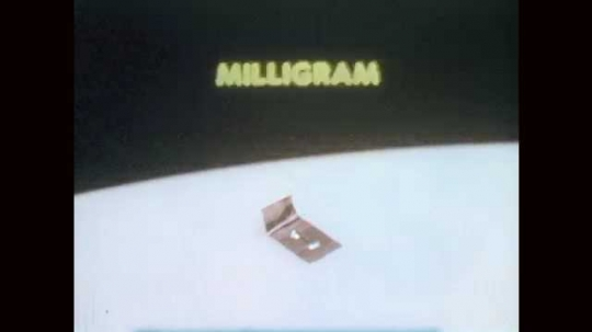 1970s: Close up of metal piece, word on screen. Metal pieces, words on screen. Close up of metal piece. Scale on table.