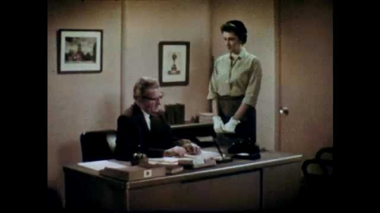 1960s: Man with glasses sits behind desk. Woman stands at desk and speaks to man. Man and woman talk to each other. Woman turns and exits office.