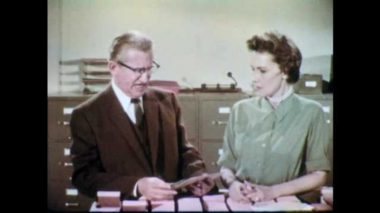 1960s: Man with glasses speaks and looks at files. Man gesticulates with hand and speaks angrily. Woman responds to man with glasses. Man replies to woman.