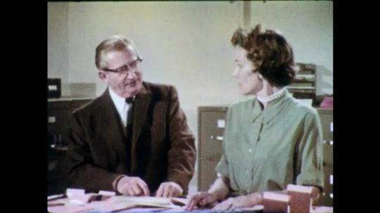 1960s: Man with glasses speaks intently to woman. Woman responds. Woman watches man leave office.