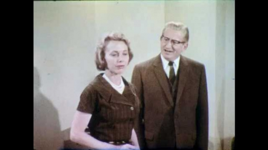 1960s: Man with glasses and woman stand in office and talk. Woman replies to man and leaves office. Man smiles to self and walks through office.