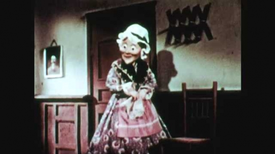 1940s: animated woman wipes face with handkerchief, exits houses. Woman walks away. Title card