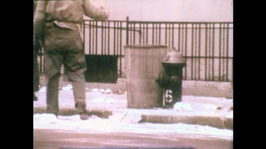 1970s: Garbage man stands next to garbage can on side of road as several people and cars pass. Line of garbage cans against an alley wall.