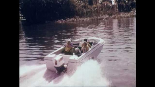 1970s: Small recreational boat speeds through the water, people on board smile and look around.