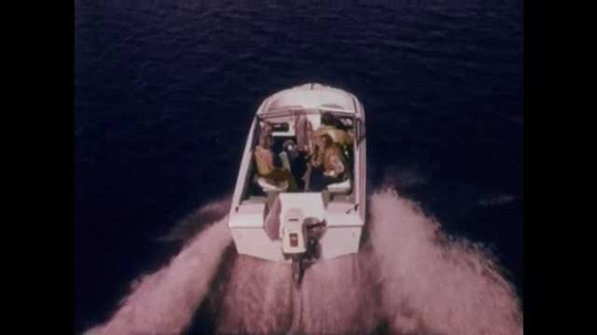 1970s: Group of people on small recreational boat as it speeds through the water. Outboard motor on boat. Boat slowly approaches the shore of lake. Motor on boat lifted from water, white propeller.