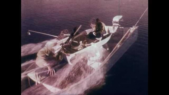 1970s: Two men on small fishing boat, one points while referring to map, the other turns around and starts motor, boat speeds off.