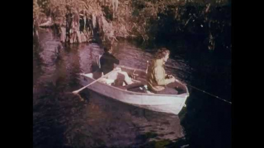 1970s: Two men on boat fishing, boat slowly drifting through water. Man and woman waterskiing behind boat. Car driving down road with boat on trailer.