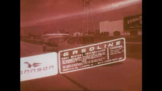 1970s: Red gasoline transfer tank being fueled as gas pump, man screws lid on. Man launches boat from trailer, boy with rope prevents boat from drifting off.